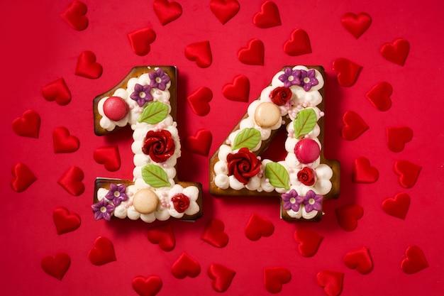 Gâteau de saint valentin avec forme de nombre et coeurs sur rouge