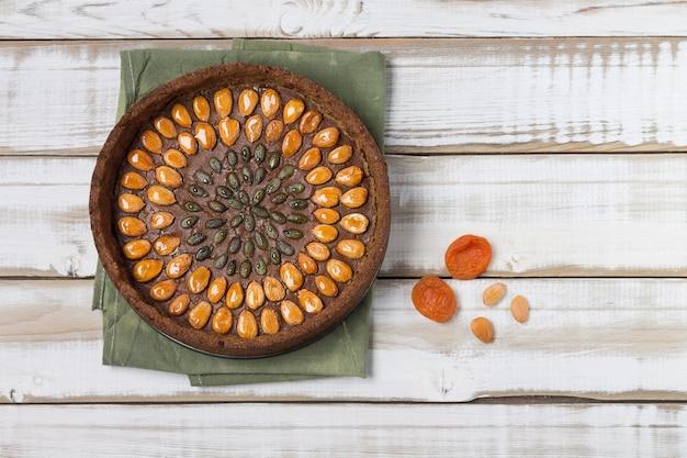 Gâteau sans gluten aux noix d'abricot et graines de citrouille, avec garniture, sur un fond en bois clair.