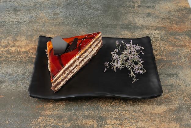 Gâteau savoureux sur assiette avec fleur sur surface en marbre.