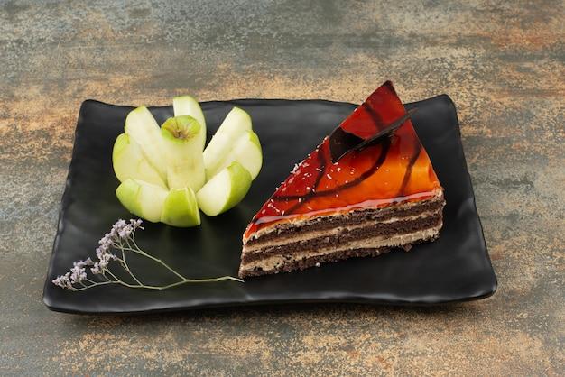 Gâteau savoureux sur assiette avec pomme verte hachée sur une surface en marbre.