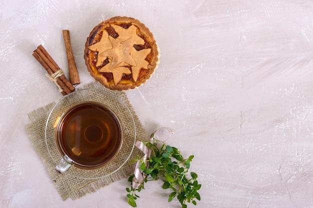 Gâteau sucré aux abricots - tartelette de pâtisserie remplie de confiture et une tasse de thé à la cannelle. vue de dessus.