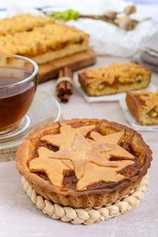 Gâteau sucré aux abricots - tartelette de pâtisserie remplie de confiture et une tasse de thé à la cannelle