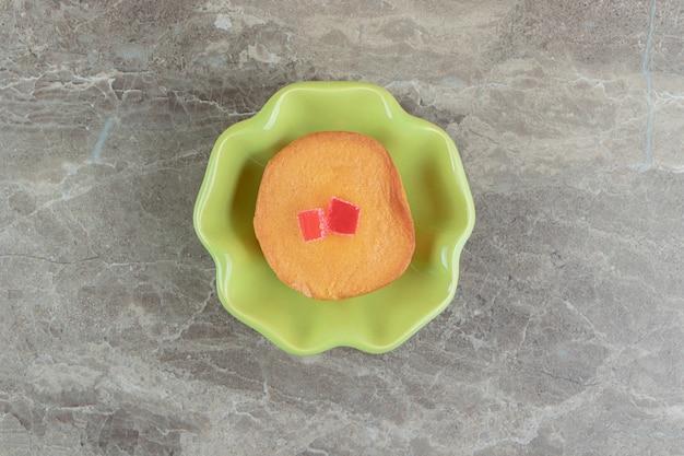 Gâteau sucré avec des bonbons dans un bol vert