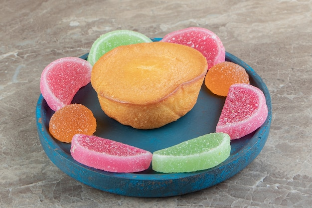 Gâteau sucré et bonbons à la marmelade sur plaque bleue