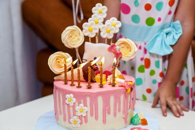 Gâteau sucré avec des bougies allumées pour l'anniversaire des enfants, des bonbons pour la fête des enfants