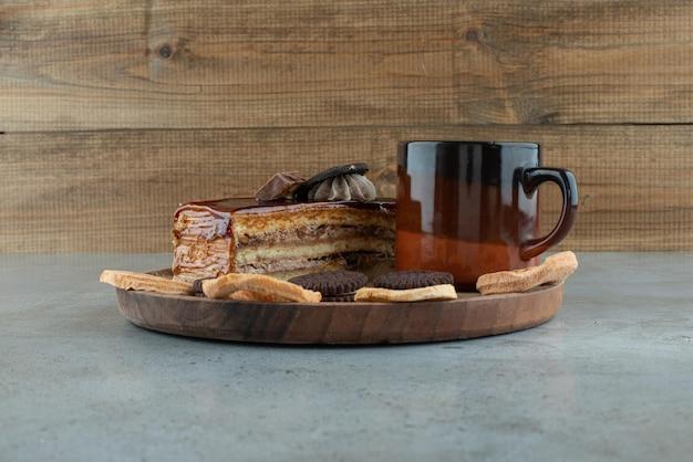 Gâteau sucré, fruits secs et tasse de café sur une assiette en bois.