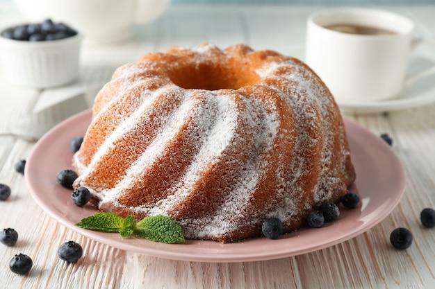 Gâteau avec sucre en poudre et myrtille sur table