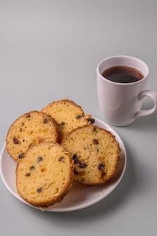 Gâteau sucré et thé sur fond gris.