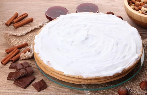 Gâteau sur support en verre et noix sur table en bois