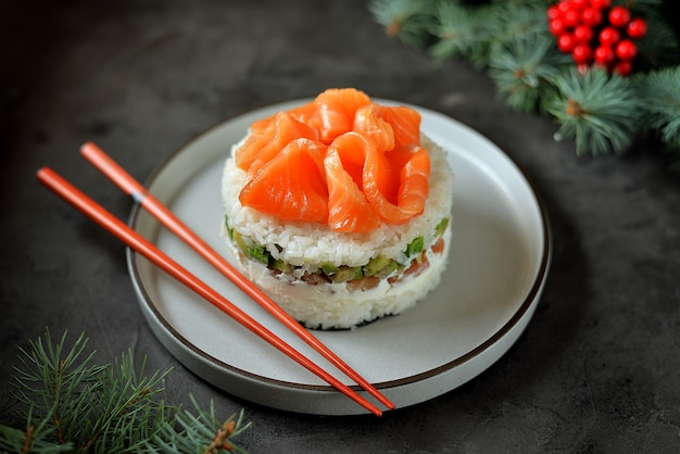 Gâteau sushi maison avec saumon légèrement salé, avocat, fromage à pâte molle et algues. surface de noël.
