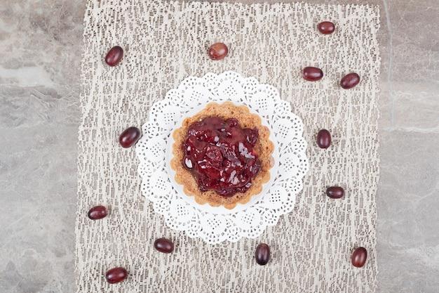 Gâteau tarte aux fruits sur toile de jute et raisins.