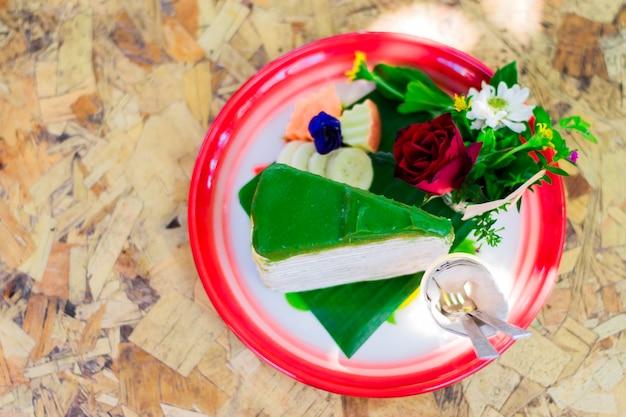 Gateau de thé vert sur plateau rouge ont des fleurs et des fruits font beau sur la table en bois