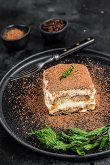 Gâteau tiramisu italien au cacao et à la menthe sur une assiette. fond noir. vue de dessus.