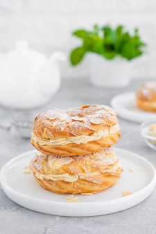 Gâteau traditionnel français paris brest avec crème pralinée, sucre en poudre et pétales d'amandes sur une assiette