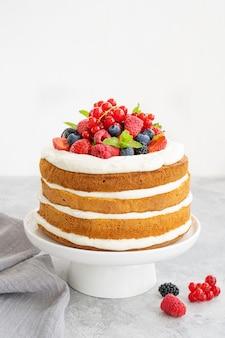 Gâteau à la vanille en couches nue fait maison avec de la crème fouettée et des baies fraîches sur le dessus