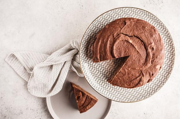 Gâteau végétalien au chocolat sur un plat blanc pour gâteau, vue de dessus, espace copie.