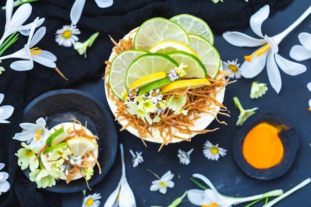 Gâteau végétalien cru au citron et citron vert sur une surface noire recouverte de petites fleurs de marguerite