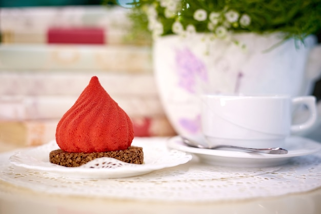 Gâteau de velours avec du thé sur la table avec des fleurs et des livres.
