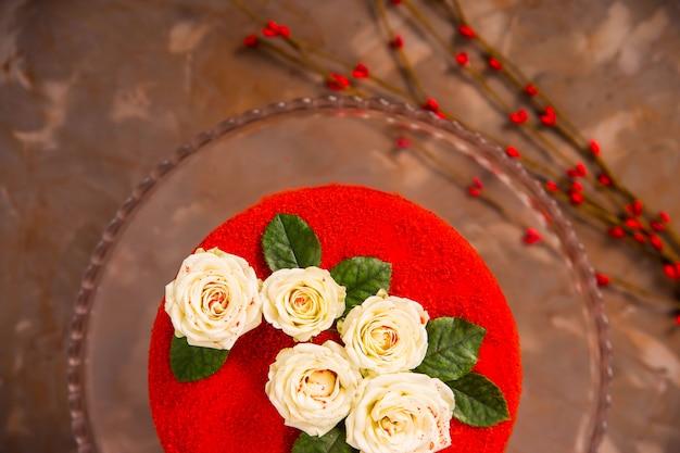 Gâteau velours rouge décoré de petites roses blanches à feuilles vertes