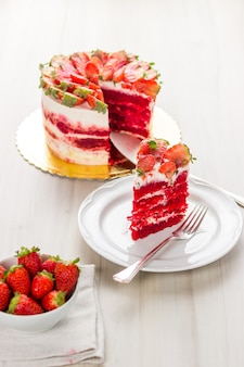 Gâteau de velours rouge sur fond en bois blanc. aux fraises.