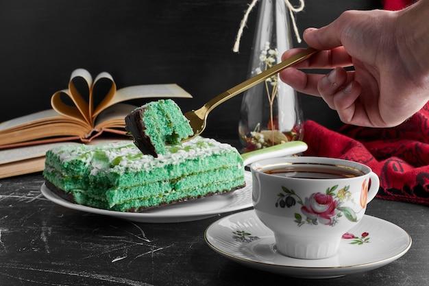 Gâteau vert à la pistache et à la menthe avec une tasse de thé.
