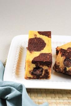 Gâteau de voyage en marbre, mini gâteau en marbre avec du chocolat fondu à l'intérieur. également connu sous le nom de gâteau de tube. servi sur plaque blanche avec copie espace pour le texte