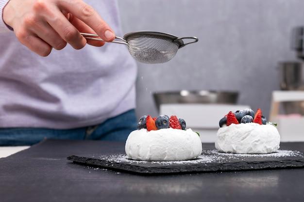 Gâteaux anna pavlova. le chef pâtissier saupoudre le sucre glace sur les gâteaux aux petits fruits.
