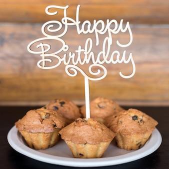Gâteaux d'anniversaire et muffins avec panneau de voeux en bois sur mur rustique. chante en bois avec des lettres joyeux anniversaire et bonbons de vacances.
