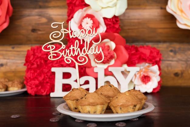 Gâteaux d'anniversaire et muffins avec panneaux de voeux en bois sur mur rustique. chante en bois avec des lettres joyeux anniversaire, bébé et bonbons de vacances.