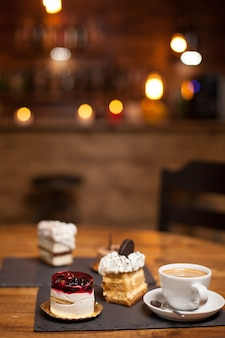 Gâteaux assortis pour le dessert sur une table en bois dans un café. gâteaux avec des ingrédients naturels. délicieuse tasse de café. gâteaux aux saveurs différentes.