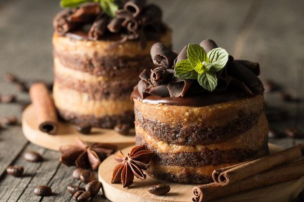 Gâteaux au chocolat noir sur planche à slattern noir à la menthe, la cannelle, les grains de café sur un fond en bois. concept de nourriture savoureuse dessert.