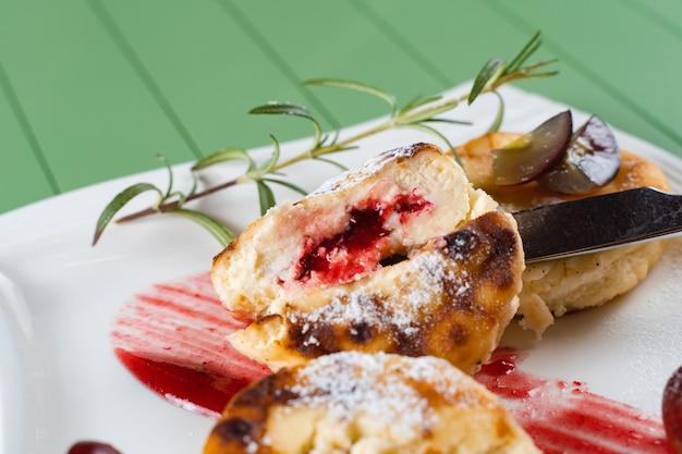 Gâteaux au fromage coupés avec des baies, décorés avec du sucre en poudre, une branche de romarin et des raisins avec de la confiture de baies sur une assiette blanche. délicieux petit-déjeuner au fromage cottage.