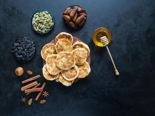 Gâteaux au fromage avec du miel, des dattes et du café sur la table.