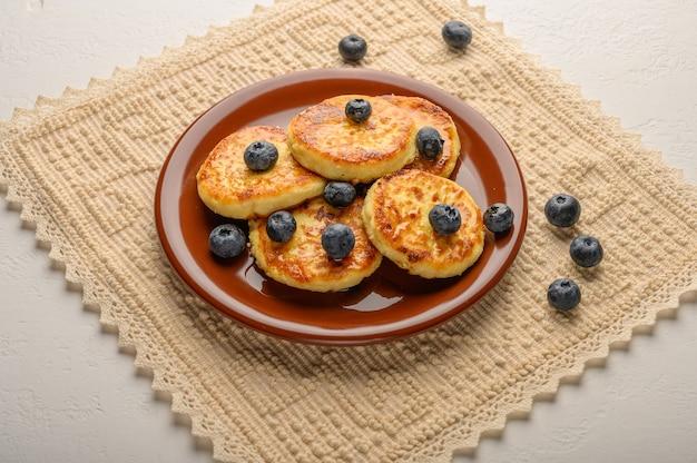 Gâteaux au fromage faits maison sur une assiette sur une serviette en lin avec des baies et du sirop libre
