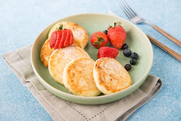 Gâteaux au fromage frits faits maison avec du lait concentré et des baies, mise au point sélective