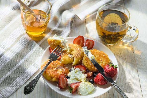 Gâteaux au fromage avec thé au miel et baies sur une table en bois