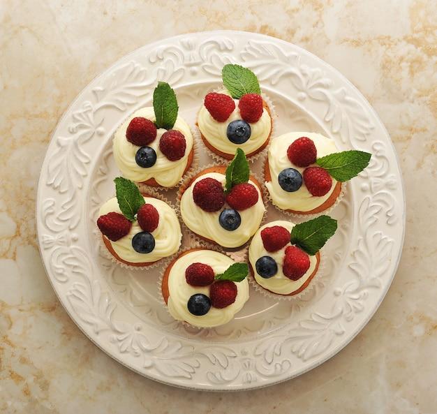 Gâteaux aux framboises et myrtilles sur une assiette