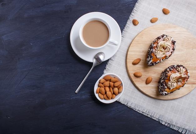Gâteaux aux pépites de chocolat et décorations à la crème sur une planche en bois noire en bois.