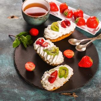 Gâteaux colorés à la crème de chantilly, fruits et baies sur fond en bois bleu grunge