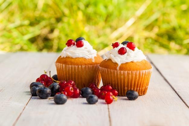 Gâteaux à la crème et aux baies sur des planches en bois