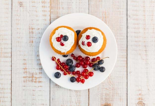 Gâteaux à la crème et aux baies sur des planches de bois
