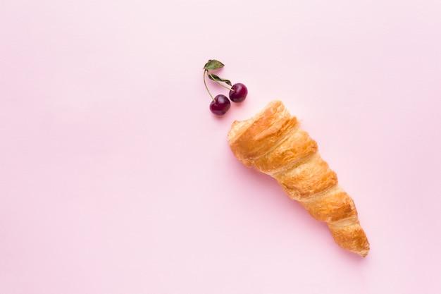 Gâteaux à la crème avec des cerises sur rose
