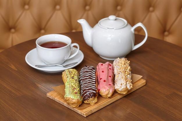 Gâteaux éclair colorés avec crème et théière sur planche de bois