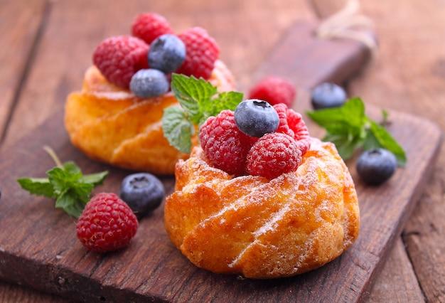 Gâteaux éponge aux framboises et bleuets sur une planche de bois