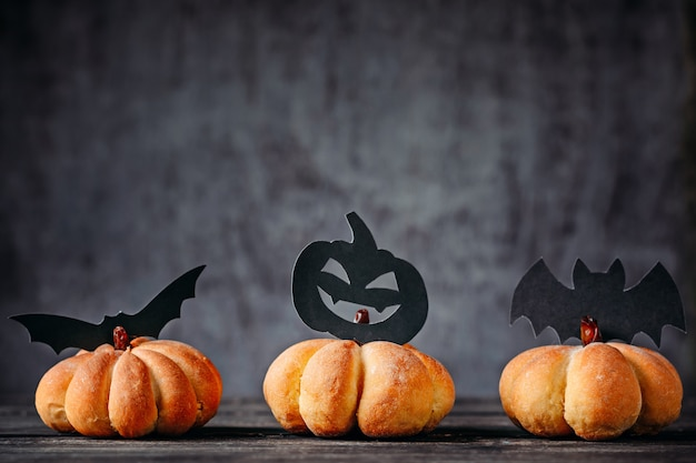 Gâteaux faits maison en forme de citrouille et décorations d'halloween sur fond sombre