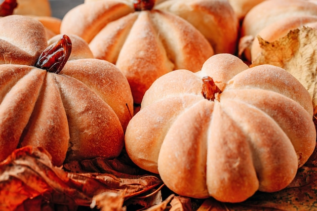 Des gâteaux faits maison en forme de citrouille avec les feuilles de l'automne se bouchent. concept de bonbons d'halloween