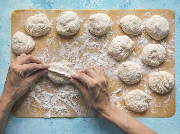 Gâteaux faits maison de la pâte dans les mains des femmes. le processus de fabrication de tartes à la main avec de la pâte de chou.