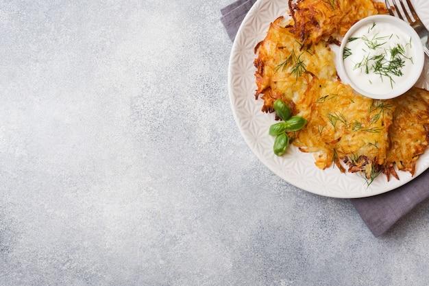 Gâteaux frits de pommes de terre râpées sur l'assiette avec la sauce, pancakes traditionnels boxty raggmunk