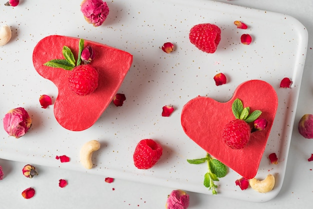 Gâteaux ou gâteaux au fromage végétaliens crus en forme de cœur avec des framboises fraîches, de la menthe et des fleurs séchées. vue de dessus