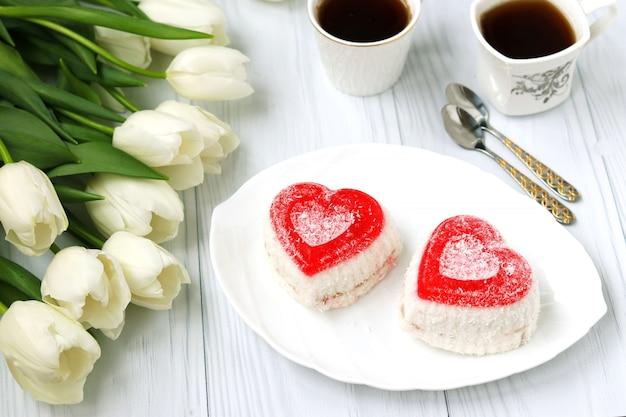 Gâteaux de gelée en forme de coeur, café et tulipes sur fond blanc, gros plan